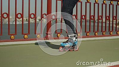 Os pés da mulher nos patins de rolo que montam fora video estoque