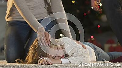 Os pais de inquietação que afagam pouca filha que dorme perto da árvore X-mas chanfram presentes da espera filme