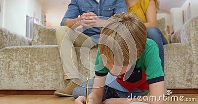 Os pais que olham seu filho fazem trabalhos de casa video estoque