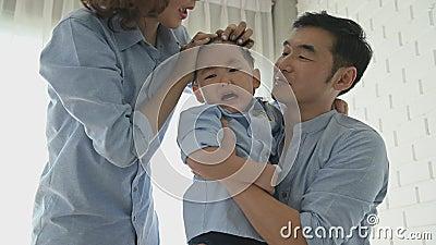 Os pais vieram confortar um menino meio japonês depois de escorregar e sua cabeça bateu no chão até que ele chorou Feliz família  vídeos de arquivo