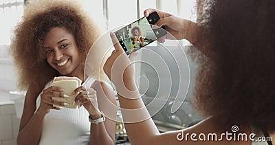 Os pares de mulher têm o divertimento fazendo fotos para meios sociais e têm o divertimento que levanta com sanduíche