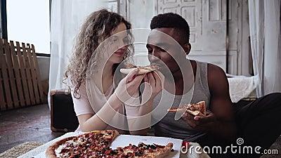 Os pares multirraciais têm o divertimento durante a refeição Alimentação da mulher o homem uma fatia de pizza Homem e fast food f filme