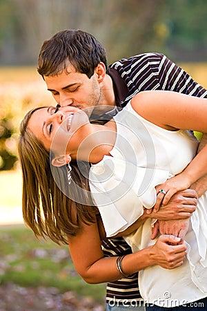 Os pares novos no amor compartilham de um abraço do divertimento