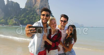 Os povos agrupam na praia que toma a foto de Selfie em homens do telefone esperto da pilha e em turistas alegres felizes de abraç video estoque