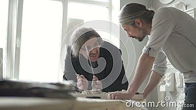 Os restauradores masculinos dos arquitetos estão funcionando no projeto na tabela na oficina moderna filme