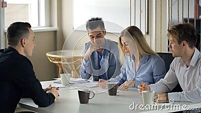 Os trabalhadores de escritório encontram-se durante a ruptura de café para discutir trabalhar detalhes filme