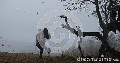Otoño oscuro, paisaje de la montaña El hombre gira a la mujer antes de árboles con las hojas caidas cubiertas con niebla pesada almacen de metraje de vídeo