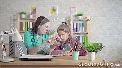 Otolaryngologist доктора объясняет слух - поврежденный подросток о слуховом аппарате видеоматериал