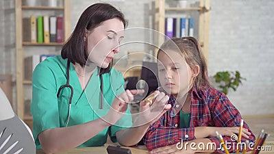 Otolaryngologist доктора объясняет слух - поврежденный подросток о слуховом аппарате c сток-видео