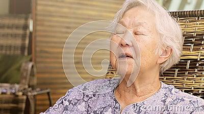 Oude dame die aan de camera, gezette het vertellen verhalen richten, die een gesprek, uitdrukkingen hebben van een oude dame stock videobeelden