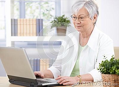 Oude dame die laptop met behulp van