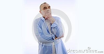 Oude man kijkt naar camera, denkt, geïsoleerd op witte achtergrond Mensen oprechte emoties, levensstijlconcept stock videobeelden