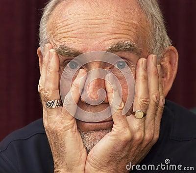 Oude mens die in ruimte met kin in handen staart
