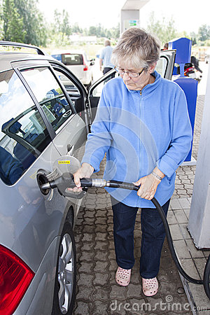 Oude vrouw die auto van brandstof voorzien