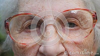 Oude vrouw die in oogglazen camera onderzoeken Ogen van een bejaarde dame met rimpels rond hen Sluit omhoog portret van stock videobeelden