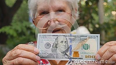 Oude vrouw in oogglazen die honderd dollarrekening in camera en openlucht glimlachen tonen Gelukkige grootmoederholding stock footage