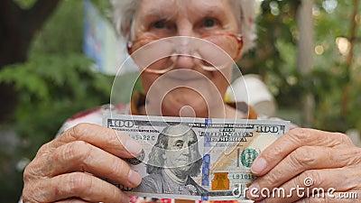 Oude vrouw in oogglazen die honderd dollarrekening tonen in camera openlucht Gelukkige grootmoeder die vreemde valuta houden stock footage