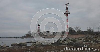 Oude vuurtoren en radiotoren door het overzees in bewolkt de herfstweer stock video