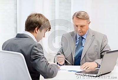 Oudere mens en jonge mens die vergadering in bureau hebben