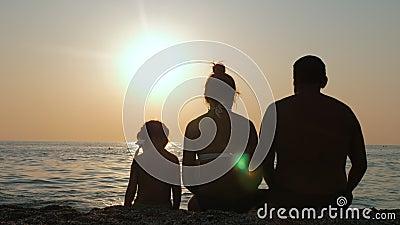 Ouders met hun kind genieten van de zonsondergang van de zee of de oceaankust stock footage