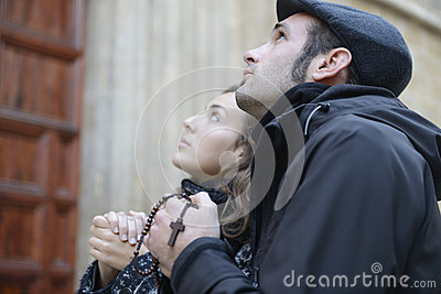 Oung couple praying to god using prayer beads