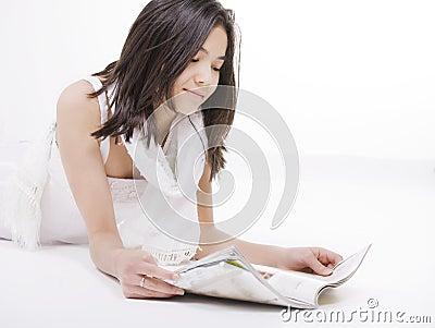 Oung teen girl in white dress reading on floor