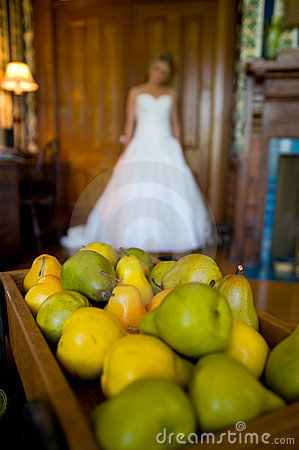 Out-of-focus bride behind a tray of pears
