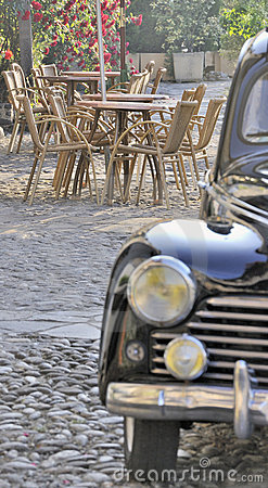 Outdoor cafe scene with old car
