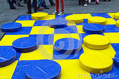 Outdoor checkers game figures yellow blue people