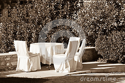 Outdoor empty summer cafe table with chairs