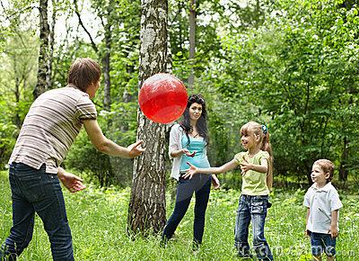 Outdoor happy family plaing ball .