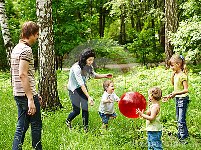 Outdoor happy family plaing ball .