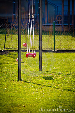 Outdoor playground with swing on green grass