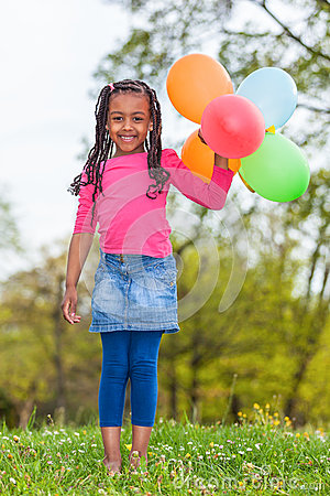 Outdoor portait of a cute young  little black girl playing with