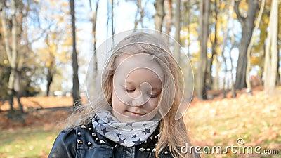 Outdoor-Portrait eines süßen 5-jährigen Mädchens mit langen blonden Haaren in einem Herbstpark stock video