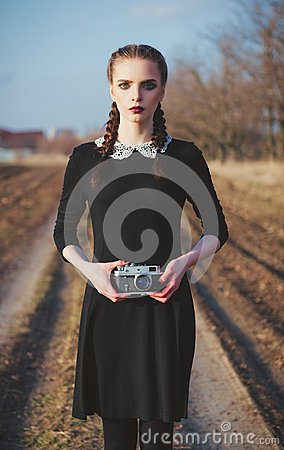 Free Outdoor Portrait Of Cute Young Girl In Old-fashioned Black Dress With Vintage Film Camera In Hands Stock Photos - 107602493