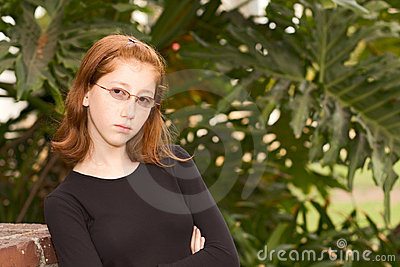 Outdoor portrait of redhead teen girl in glasses