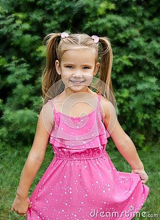 Outdoor portrait of smiling little girl holding flower