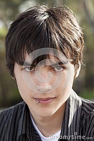Outdoor portrait teen caucasian boy dark hair