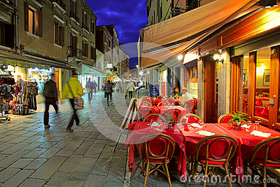 Outdoor restaurant on narrow street in Venice, Italy.