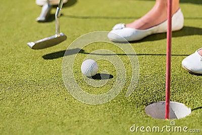 Люди играя миниатюрный гольф outdoors