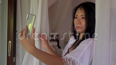Holiday lifestyle portrait of young beautiful and happy Asian Korean woman having morning coffee taking selfie with mobile phone. Outdoors holiday lifestyle stock video