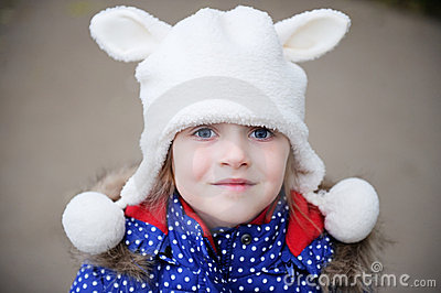 Outdoors portrait of a child girl in warm hat