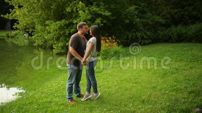 Outdoors portrait of the lovely couple kissing at the city park. Woman and man in love outside. Outdoors portrait of the lovely couple kissing at the city park stock video