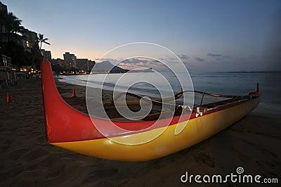 An outrigger canoe sits on the beach