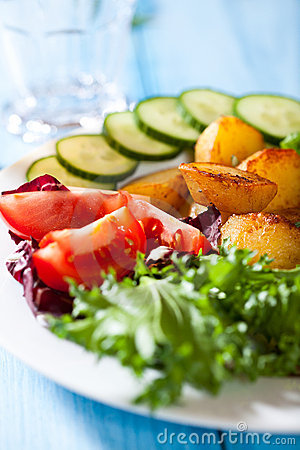 Oven baked potatoes with fresh vegetables on a pla