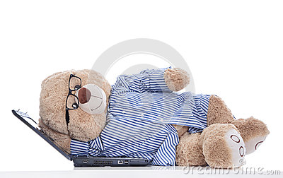 Over worked: teddy bear taking a nap on laptop isolated on white