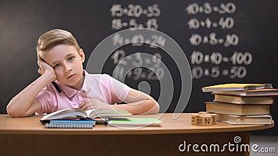 Overbelaste schooljongenzitting bij bureau en het proberen om taak moeilijke vergelijking op te lossen stock videobeelden