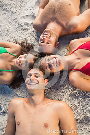 Overhead of smiling friends lying together in a circle