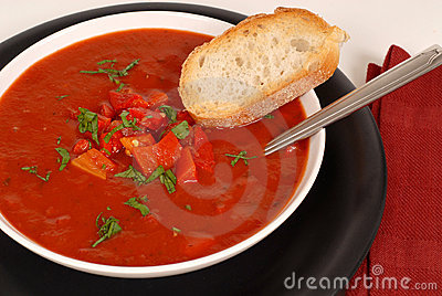 Overhead view of a bowl of tomato, red pepper and basil soup wit